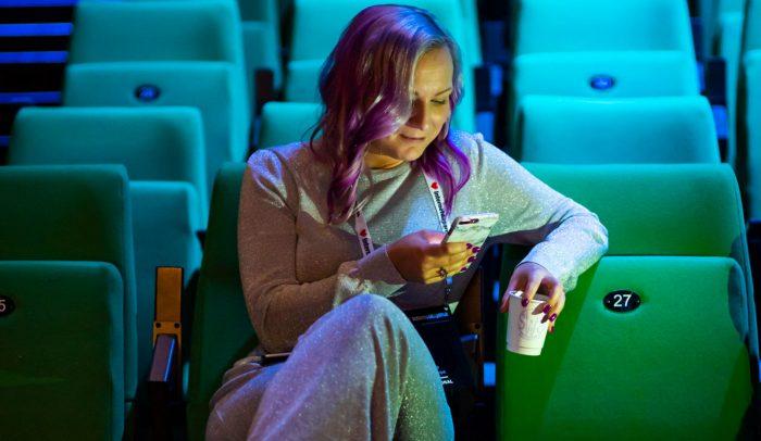Person med mobiltelefon och kaffekopp