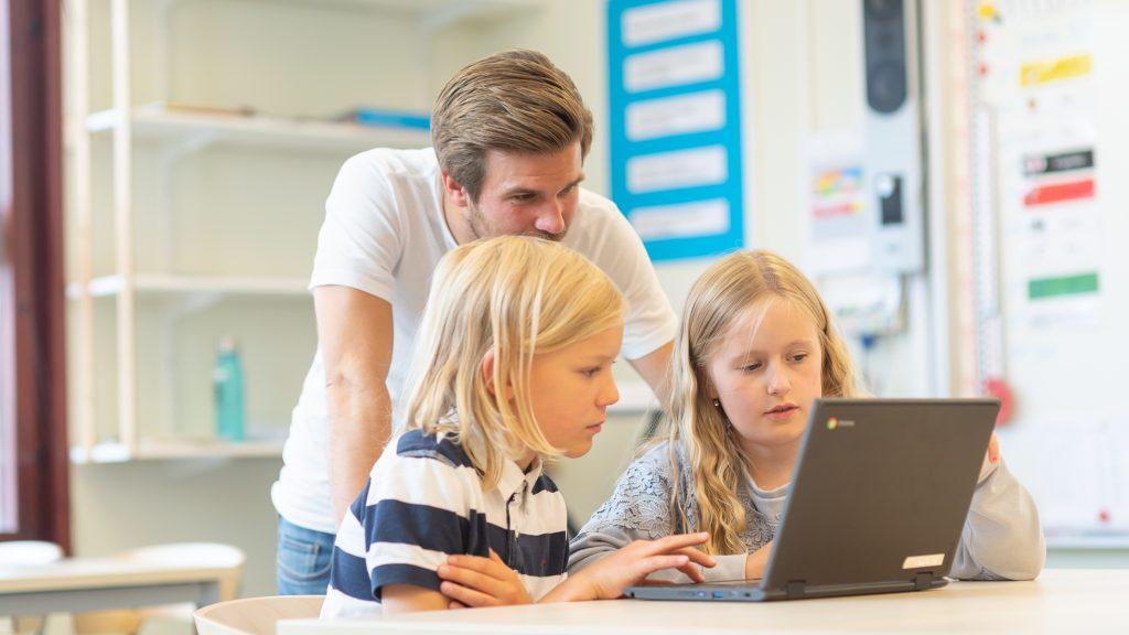 Elever jobbar med dator medan en lärare tittar på.
