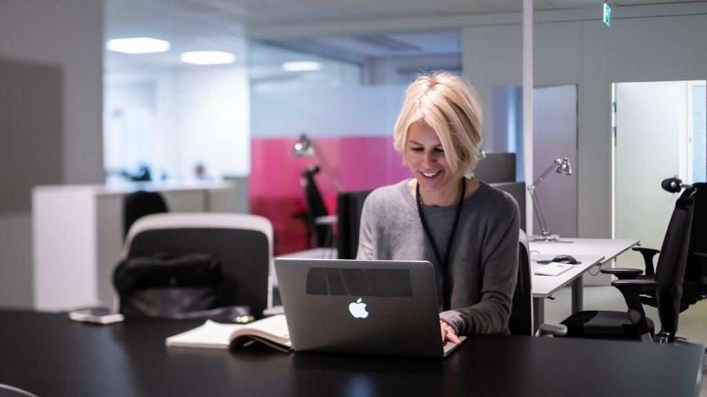 Kvinna arbetar vid dator på tomt kontor.
