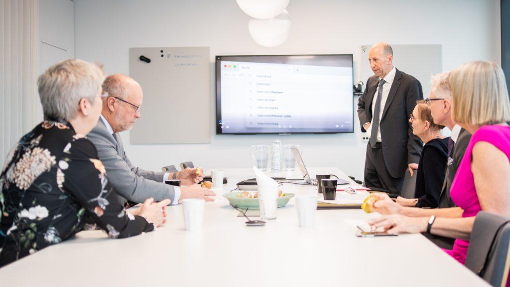 Finklädda vid långbord har möte framför presentation på skärm i mötesrum på Internetstiftelsens kontor. En av dem står upp vid sin stol.