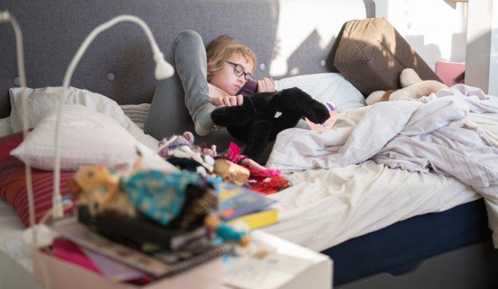 Barn ligger i säng och använder surfplatta.