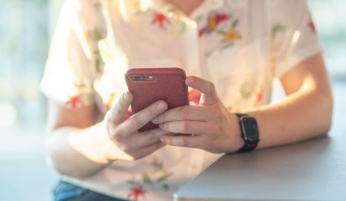 Kvinna sittandes med mobil i handen.
