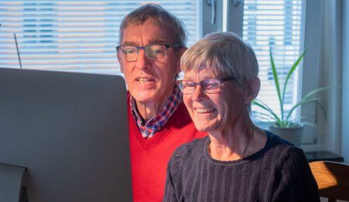 Äldre par sitter framför datorn och arbetar tillsammans
