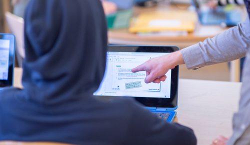 Elev vid skolbänk tittar på powerpoint på dator och får hjälp av en lärare som pekar på powerpointen.