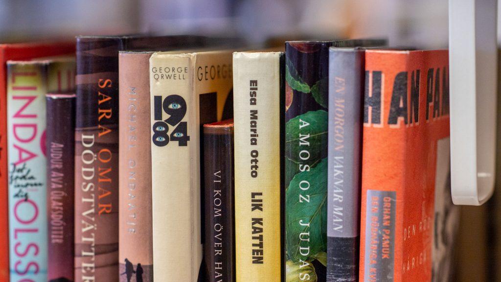 En rad med böcker i en bokhylla. Bland dem finns 1984 av George Orwell och Den rödhåriga kvinnan av Orhan Pamuk.