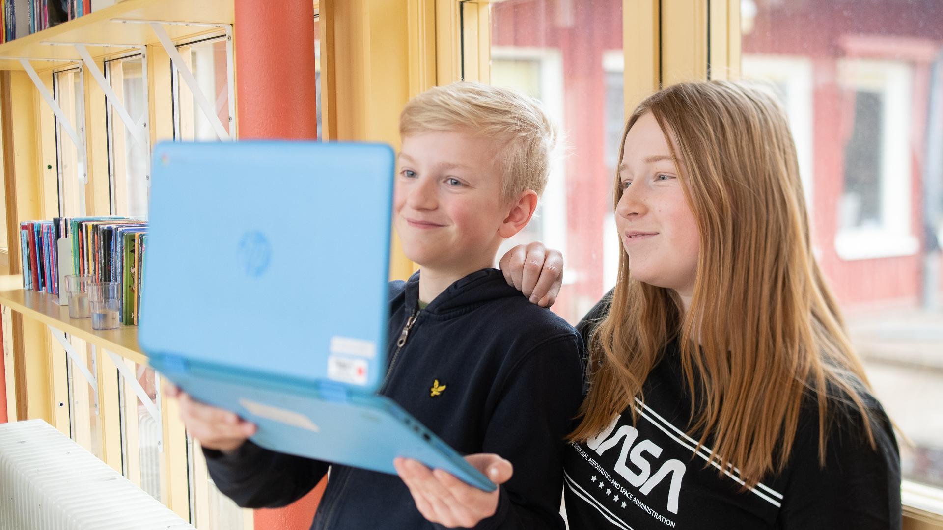 Två elever står framför en glasdörr och tittar på en dator.