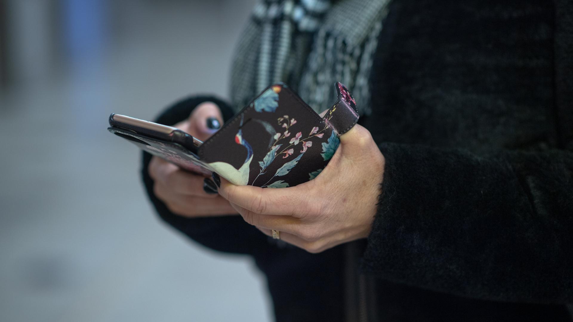 Händer använder mobiltelefon utomhus.