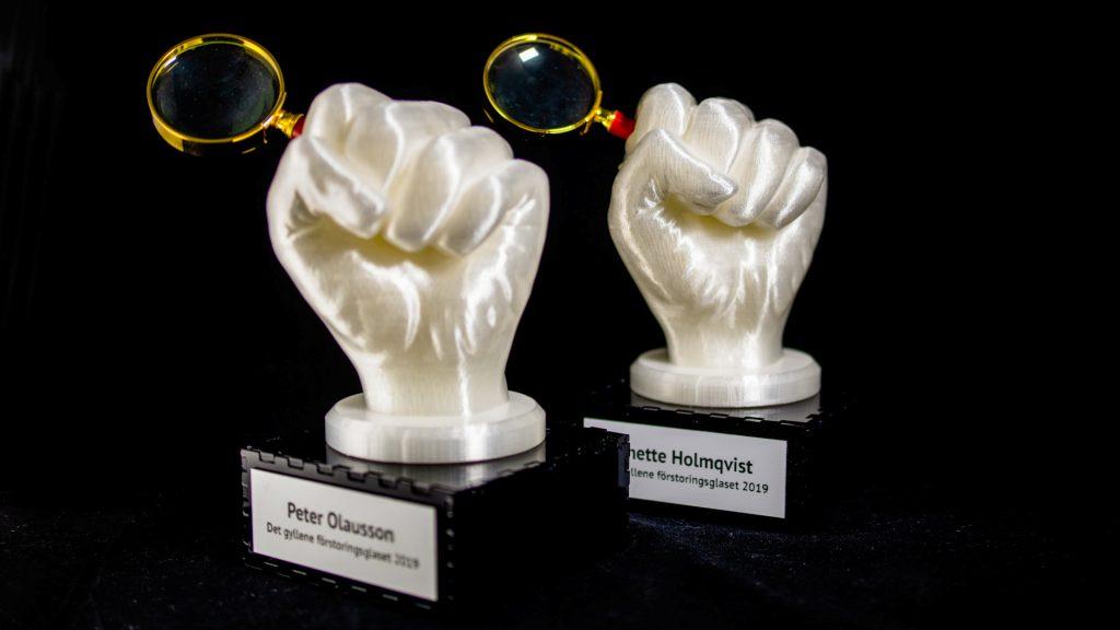 Två pokaler som vardera föreställer en näve som är knuten runt ett gyllene förstoringsglas.