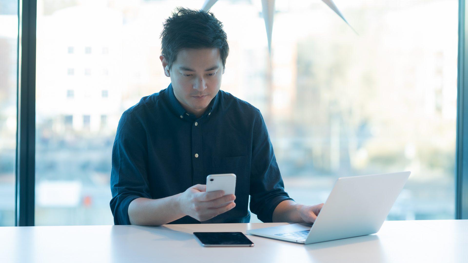Man håller en mobiltelefon i handen med en laptop och surfplatta framför sig på bordet.