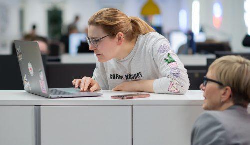Två kvinnor använder och tittar på en dator.
