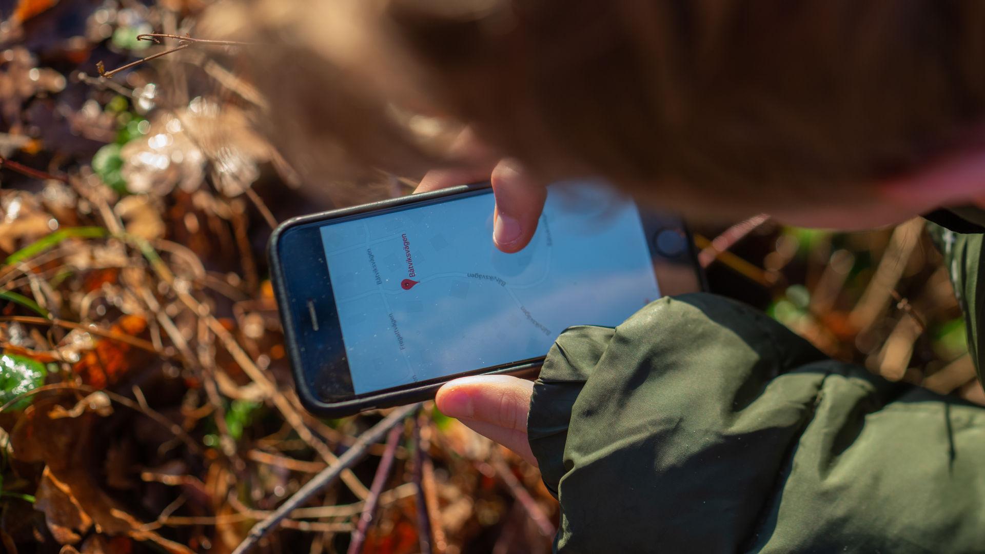 person som håller en mobil som visar en karta