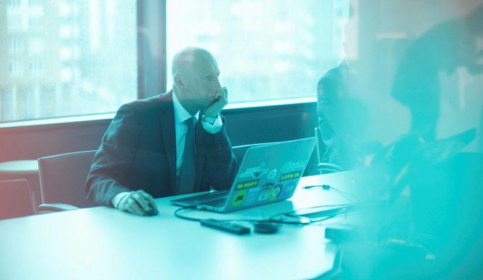 Man med kostym och slips sitter framför en laptop i ett konferensrum