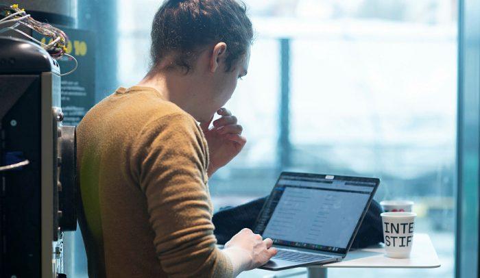 Ryggtavla av man syns stående framför en laptop.