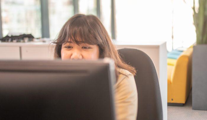 Kvinna arbetar framför dator på Internetstiftelsens kontor.