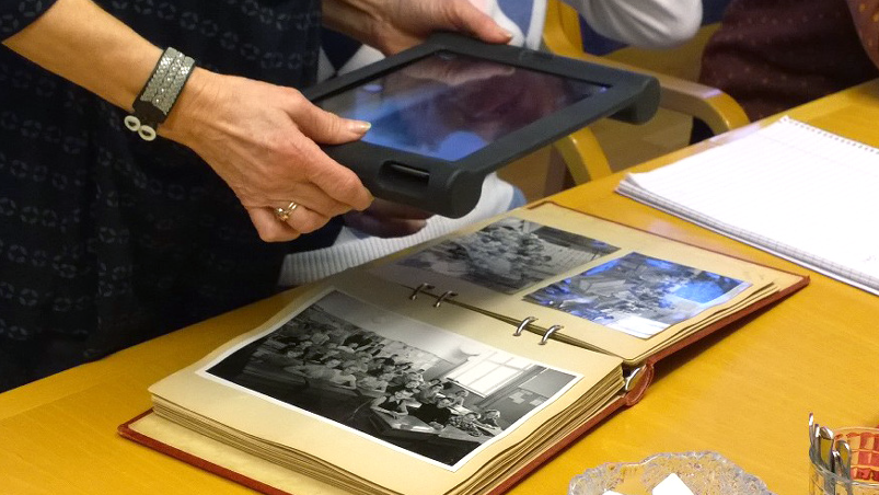 Händer med en surfplatta tar en bild i en gammal bok som ligger uppslagen på bordet.