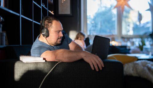 Man med hörlurar sitter i soffa i vardagsmiljö och använder dator.