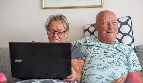 Äldre par som sitter framför bärbar datorn i soffan