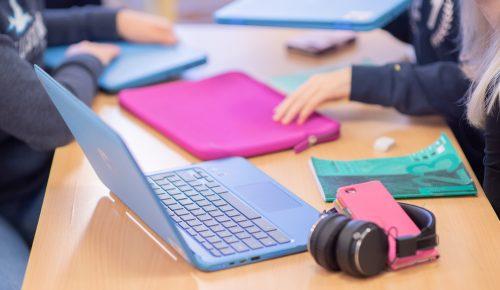 Elever sitter framför en laptop och hörlurar på en skolbänk