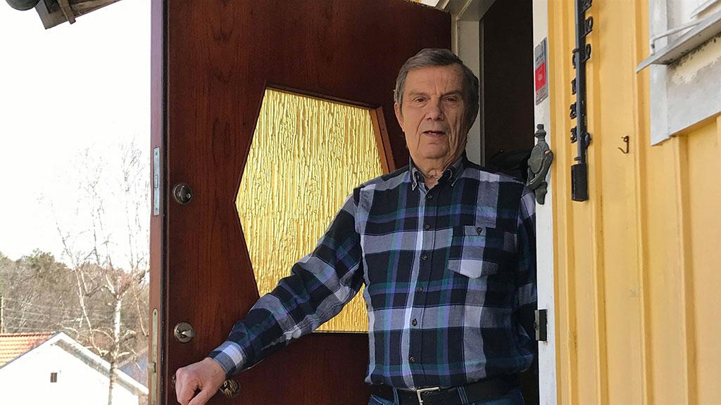 Äldre man som öppnat sin ytterdörr.