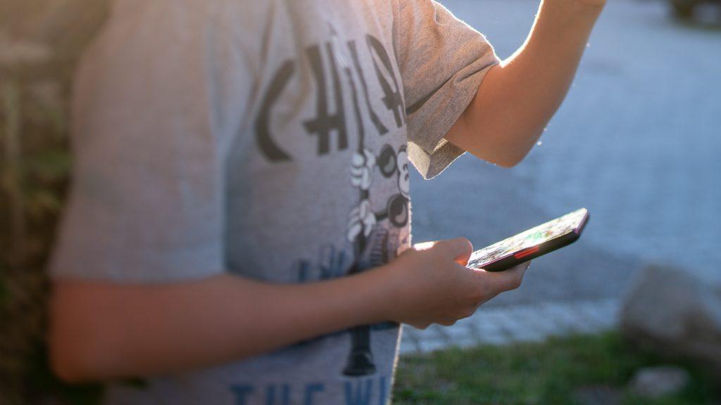 Barn som håller i en mobiltelefon.