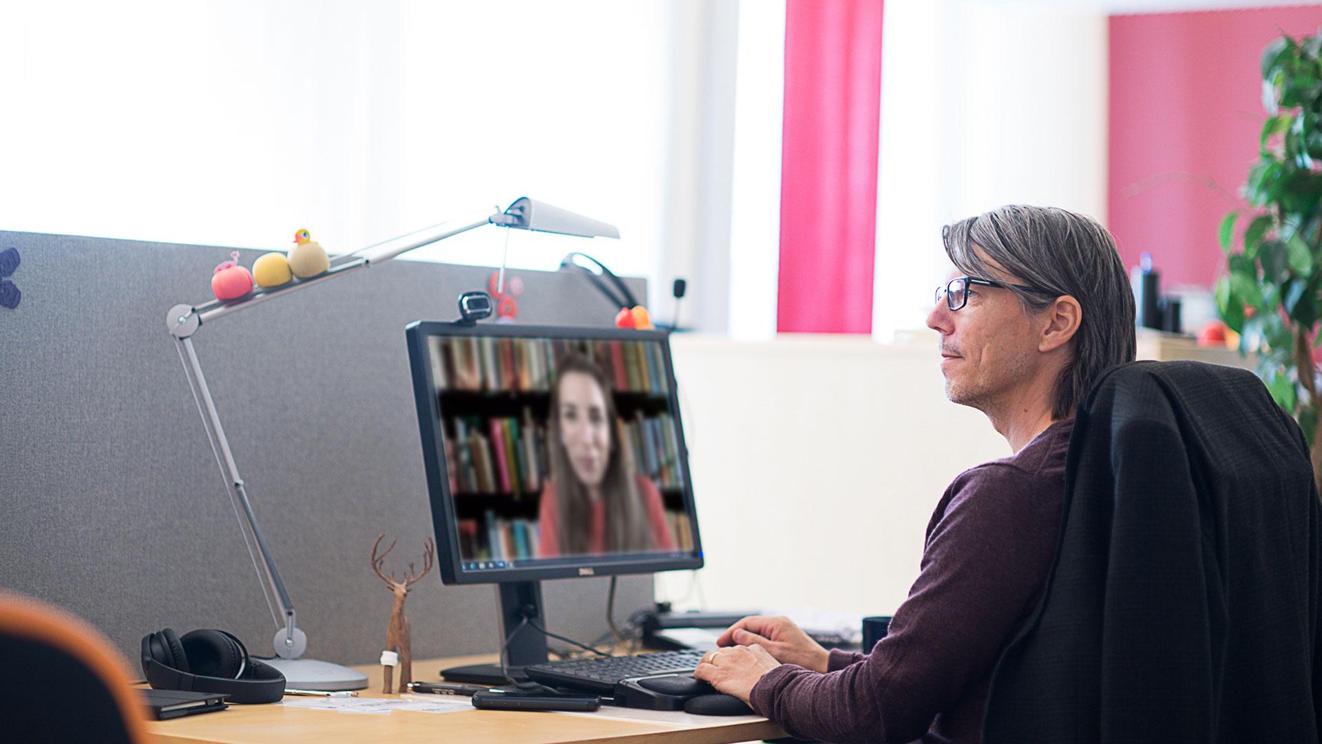 Man som sitter framför en digital föreläsning vid sitt skrivbord.