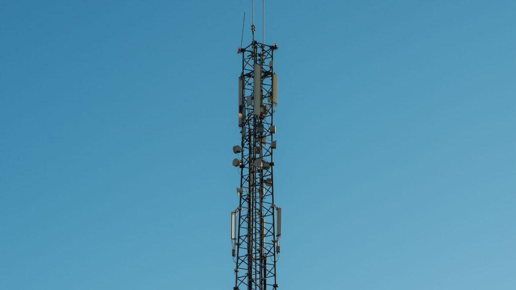 En mobilmast mot blå himmel och moln.