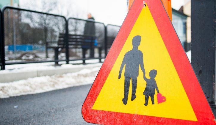 Vägskylt med vuxen och barn som håller hand. Barnet håller även i ett pixelhjärta.