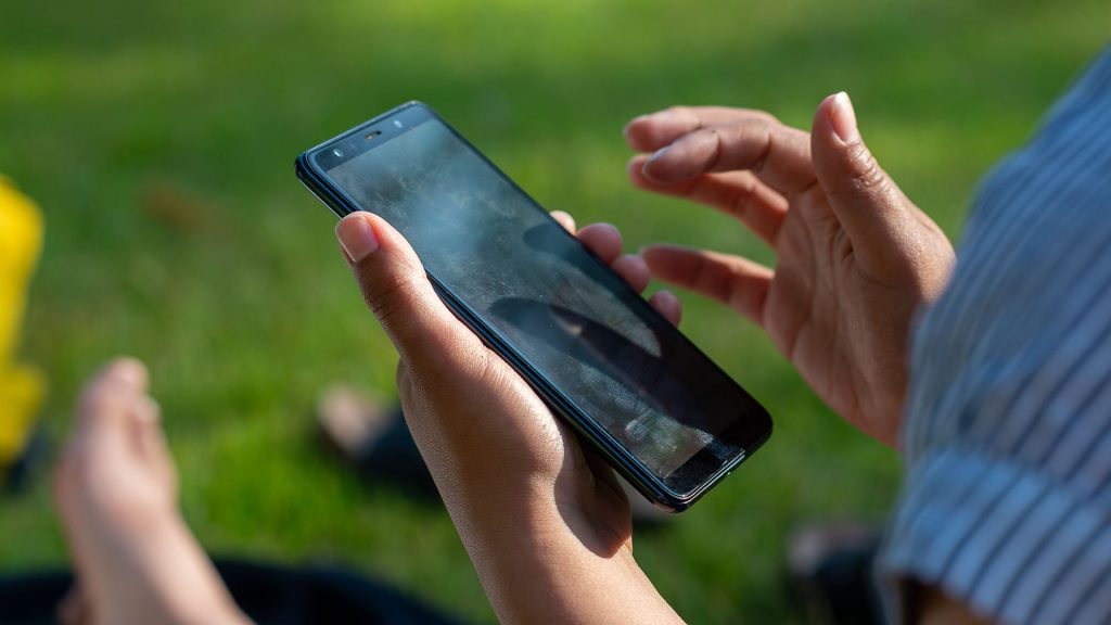 hand håller i en mobil i bakgrunden nakna fötter
