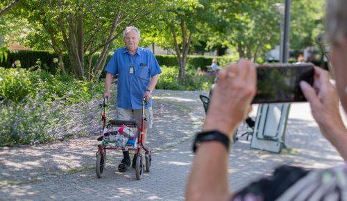 Äldre man med rullator, fotograferad av mobiltelefon.