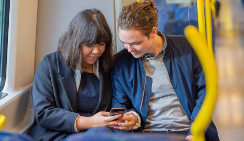 Två personer med mobiltelefon på tunnelbanan