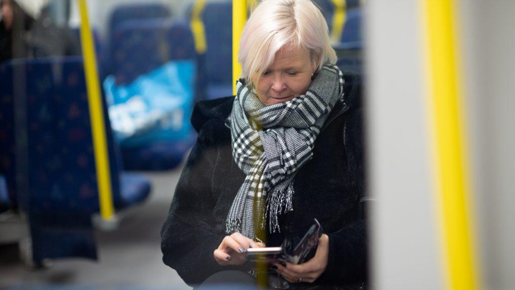 Kvinna använder mobiltelefon i tunnelbanevagn.