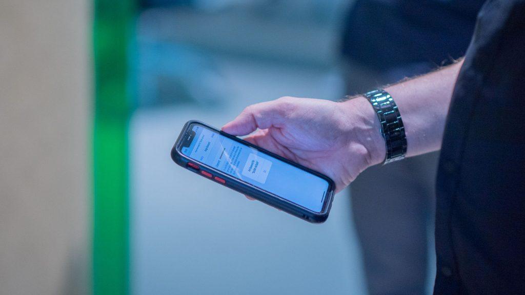 Hand som håller en mobiltelefon.