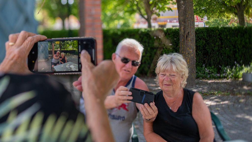 Äldre par som tittar på mobiltelefon.