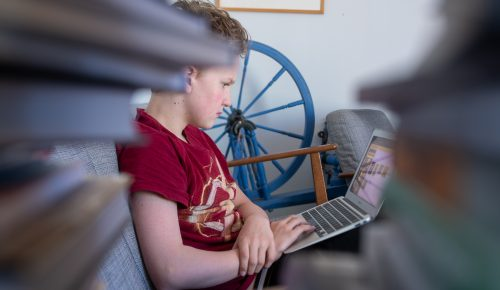 Pojke sitter i en soffa och läser på sin laptop som finns i knäet