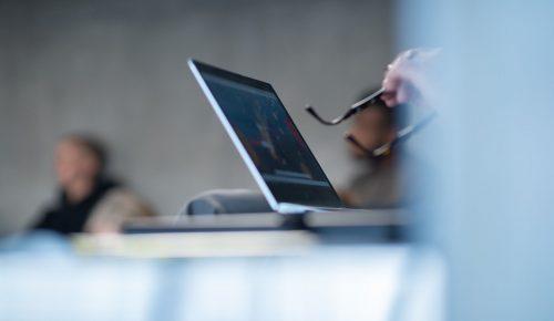 Någon som inte syns arbetar vid dator och håller i ett par glasögon.