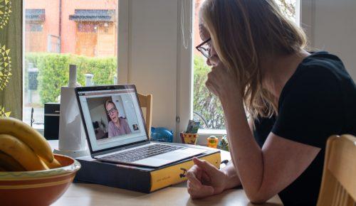 En kvinna sitter i ett videomöte vid sitt köksbord