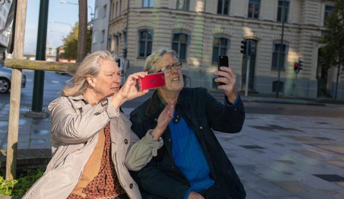Äldre par som tittar på sina mobiler ute på ett torg