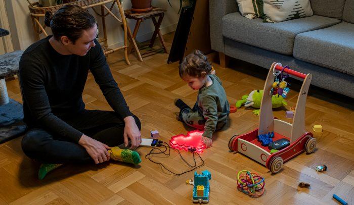 Förälder som sitter på golvet och leker med ett barn.