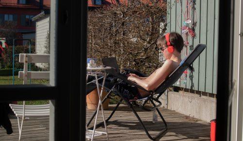 Pojke som deltar i distansundervisning i en solstol på altanen