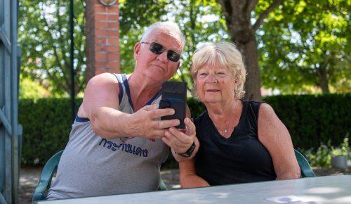 Ett äldre par tar en selfie i trädgården
