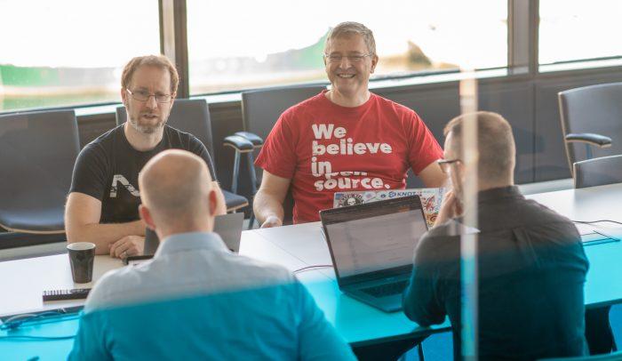 De fyra i DNS-Labs-teamet har möte runt ett bord i ett konferensrum.