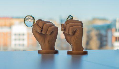 Prispokalen Det gyllene förstoringsglaset, en hand som håller i ett förstoringsglas.
