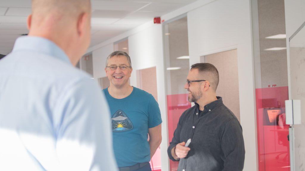 Tre män i teamet DNS-Labs har stående möte och ler mot varandra