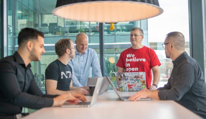 Medarbetare står och samtalar i möte med laptops