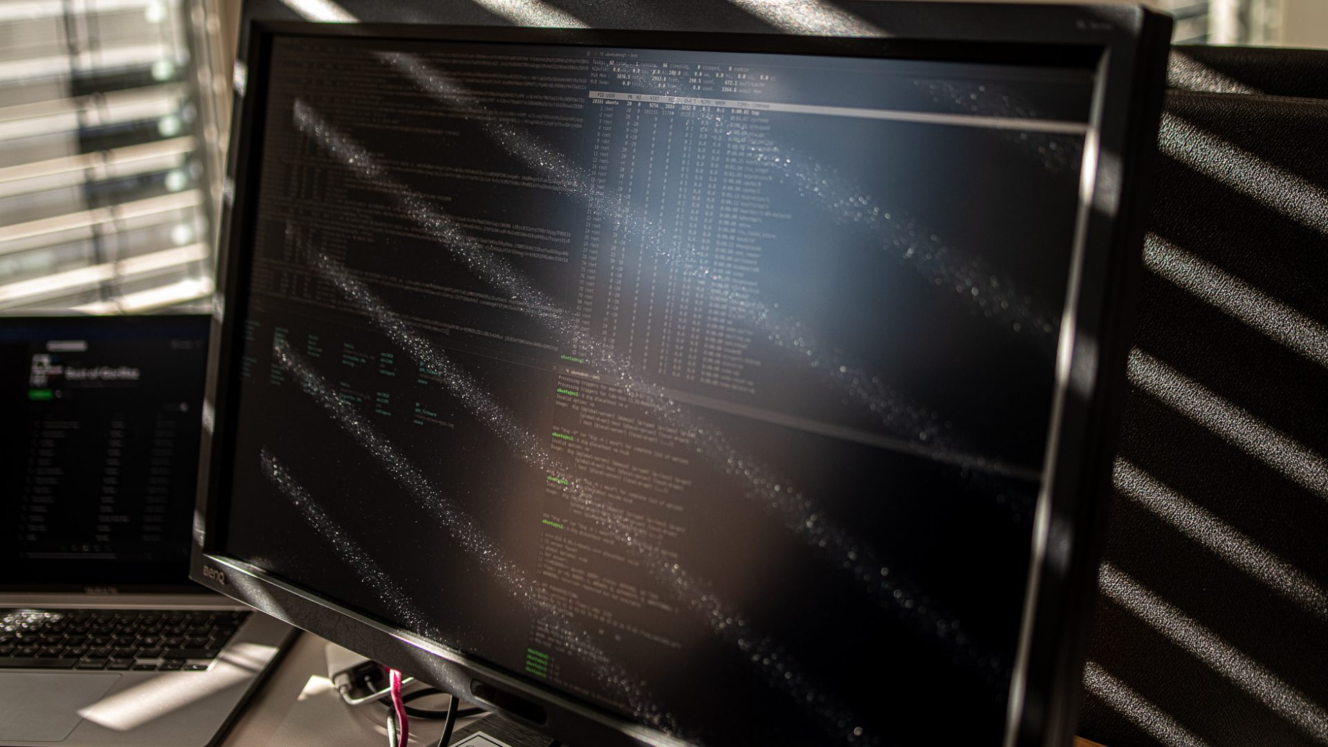 En dammig dataskärm med kod blir beslyst av solstrålar genom ett fönster med persienner på ett kontor.