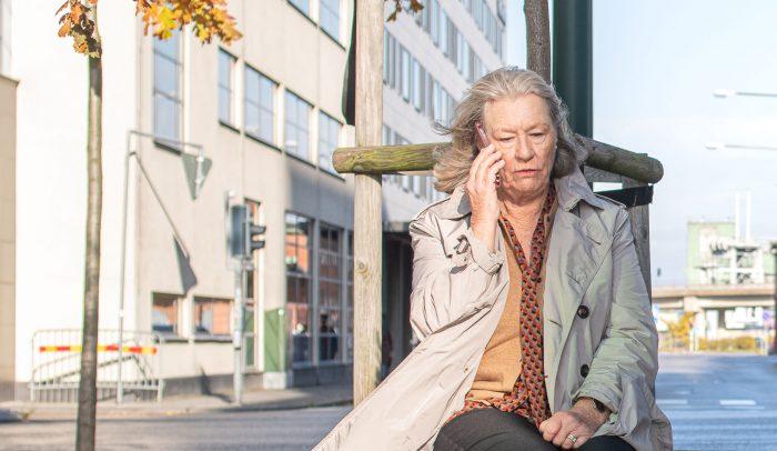 Äldre kvinna som pratar i mobiltelefon utomhus