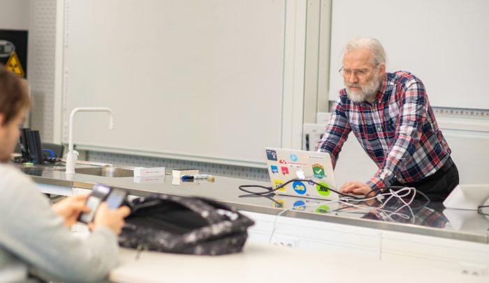 En föreläsningssal på på KTH. En föreläsare tittar på sin dator medan en student tittar på sin telefon vid ett bord.