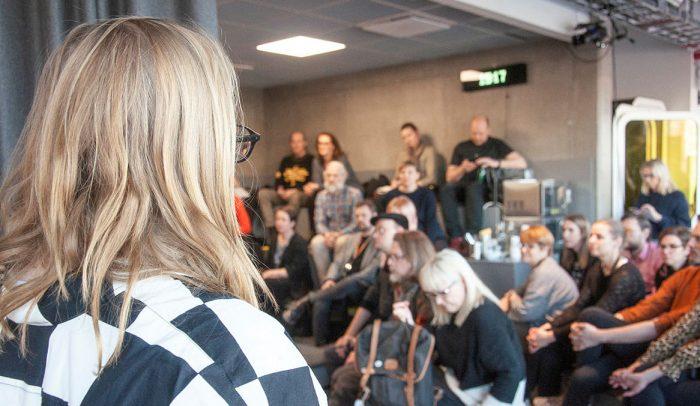 En kvinna står vänd mot en publik som sitter och lyssnar på en föreläsning i Gradängen på Goto 10 i Stockholm