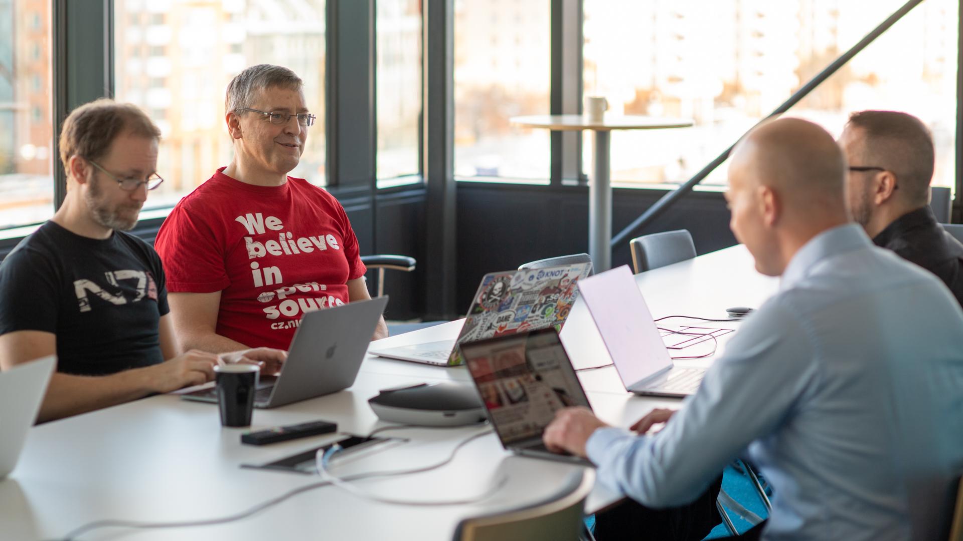 Fyra män sitter i ett konferensrum med sina laptops