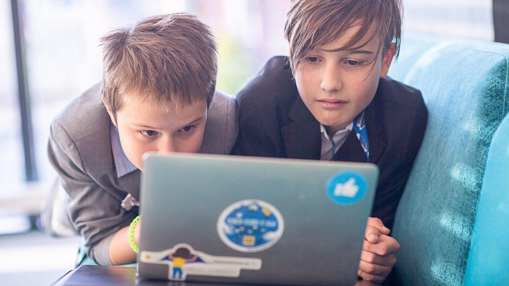 Två barn som surfar på en dator.